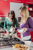 Young women in the kitchen. Young women cooking in the kitchen Stock Images