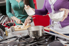 Young women in the kitchen. Young women cooking in the kitchen Royalty Free Stock Images