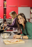 Young women in the kitchen. Young women with the glass of wine in the kitchen Stock Image