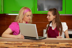 Young women in the kitchen with a laptop. Young women are talking in the kitchen with a laptop Stock Photo