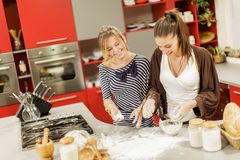 Young women in the kitchen. Young women preparing food in the kitchen Royalty Free Stock Images
