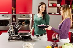 Young women in the kitchen. Young women preparing meal in the kitchen Stock Photo
