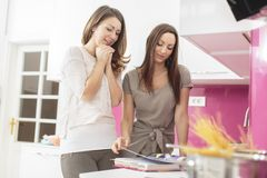 Young women in the kitchen. Young women reading book of recipes in the kitchen Royalty Free Stock Image