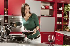 Young women in the kitchen. Young woman preparing meal in the kitchen Stock Images
