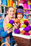 Young women in knitting shop Royalty Free Stock Photo
