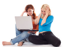 Young women with laptop. Two young women find something shocking on a laptop. Isolated on white Royalty Free Stock Image