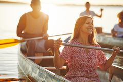 Young woman laughing while canoeing with friends on a lake stock photography