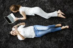 Young women laying on the carpet. With laptop and mobile phone Royalty Free Stock Image