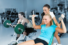 Young women lifting a dumb-bell with her  trainer Stock Image