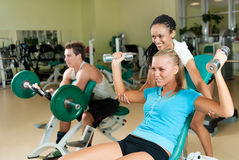 Young women lifting a dumb-bell with her  trainer Stock Images