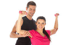 Woman with her personal fitness trainer exercising with weights Royalty Free Stock Photography