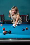 Young Women Lines Up A Shot. Young Women Lining To Hit Ball On Pool Table Royalty Free Stock Photos