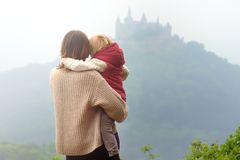 Young woman with little child admiring view of famous Hohenzollern Castle at foggy day. Family travel with little kid concept stock images