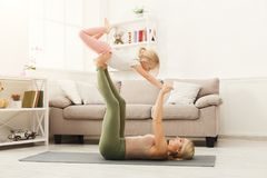 Mother and little daughter practicing acroyoga at home. Young women and little girl doing partner yoga flying pose, exercising together at home. Mother and Stock Photography