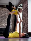 Young woman and little girl doing partner yoga flying pose exercising together royalty free stock photography