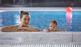 Young woman and little son resting poolside. Young women and little son resting poolside and looking at camera Royalty Free Stock Photography