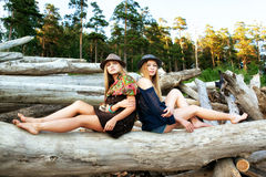Young women on logs in the forest Royalty Free Stock Photo