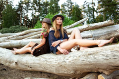 Young women on logs in the forest Royalty Free Stock Images