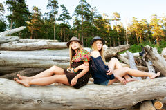 Young women on logs in the forest Royalty Free Stock Image
