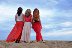 Young women in a long dress standing on the beach in summer evening. Stock Photography