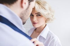 Young woman looking at camera while taking off necktie of boyfriend. Young women looking at camera while taking off necktie of boyfriend Royalty Free Stock Images