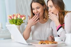 Young women looking at laptop. Two young women looking at laptop while sitting at kitchen table with cookies Stock Photos