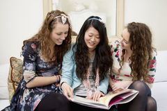 Young women looking at magazines on a sofa Royalty Free Stock Image