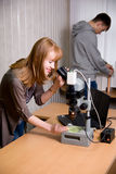 Young woman looking through microscope lense Royalty Free Stock Image