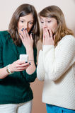 Young women looking at mobile cell phone. Two beautiful young women happy smiling looking at mobile cell phone in knitwear on white Royalty Free Stock Image