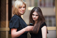 Young women looking at mobile phone Royalty Free Stock Images