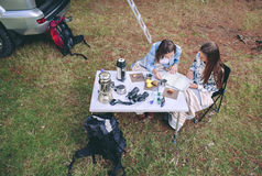 Young women looking road map in campsite Stock Photos