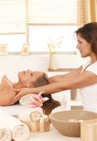 Young woman getting massage in day spa. Young women lying on bed in day spa, getting massage Stock Images