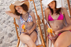 Young women lying on deck chairs while napping Stock Photos