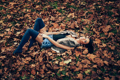 Young women lying in fallen leaves Stock Photo