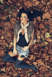 Young women lying in fallen leaves Royalty Free Stock Images