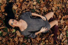 Young women lying in fallen leaves Royalty Free Stock Image