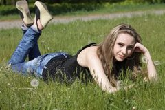 Young women lying on green grass Stock Photos