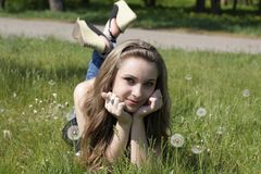 Young women lying on green grass Stock Images