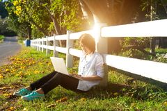 Young women lying in summer grass playing laptop and relax, sunny day, royalty free stock photo