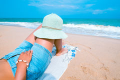 Young women lying on a tropical beach, relax and sunbathe. Leisure in summer - Young women lying on a tropical beach, relax and sunbathe. Blue sea in the Stock Image