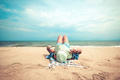 Young women lying on a tropical beach, relax and sunbathe Stock Image