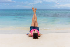 Young women lying on a tropical beach, stretching up slender leg. Young woman lying on a tropical beach, stretching up slender legs. Blue sea in the background Stock Photo