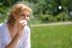 Young women makes soap bubbles Stock Photography