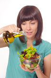 Young women making salad on white background. Young happy woman making salad with vegetables and oil.  Blue shirt. On white background Royalty Free Stock Image