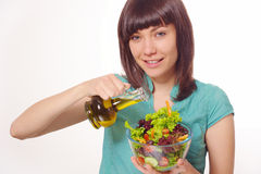 Young women making salad on white background. Young beautiful happy woman making salad with vegetables and oil.  Blue shirt. On white background Stock Photo