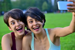 Young women making surprised face while looking at smart phone. Royalty Free Stock Photo