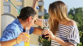 Young women and man drinking and hugging at rooftop party stock video