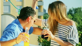 Young women and man drinking and hugging at rooftop party stock footage