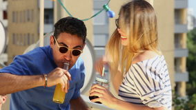 Young women and man drinking and laughing at rooftop party. Young blonde women and latino man drinking and laughing at rooftop party stock footage