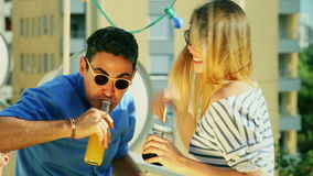 Young women and man drinking and laughing at rooftop party. Young blonde women and latino man drinking and laughing at rooftop party, graded stock footage
